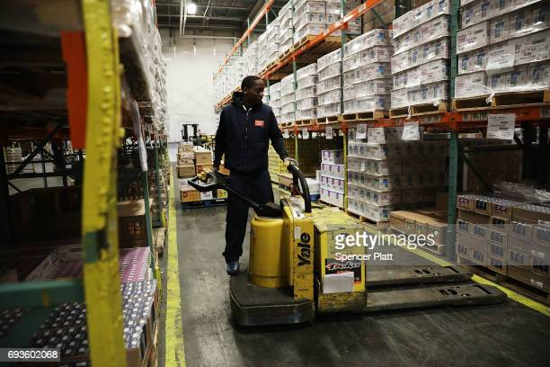 Employee Shawn Lewis moves pallets of food at the Food Bank for New York City's main warehouse in the Bronx neighborhood of Hunts Point on June 7...