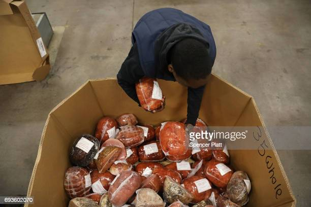 Employee Shawn Lewis packs hams at the Food Bank for New York City's main warehouse in the Bronx neighborhood of Hunts Point on June 7 2017 in New...