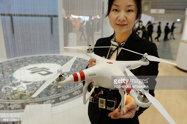 A DJI employee shows off the company's latest 'Phantom 2' radiocontrolled multicopter with small video camera at the DJI booth during the 'CP2014'...