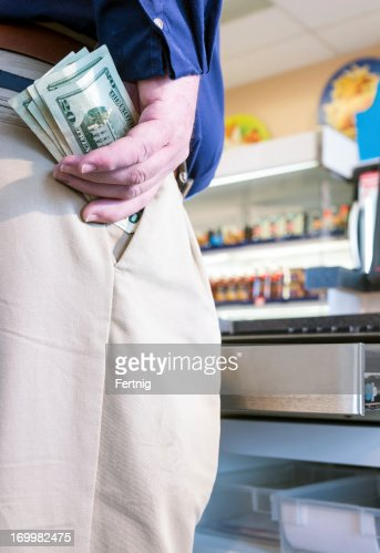 Employee stealing cash from a store register