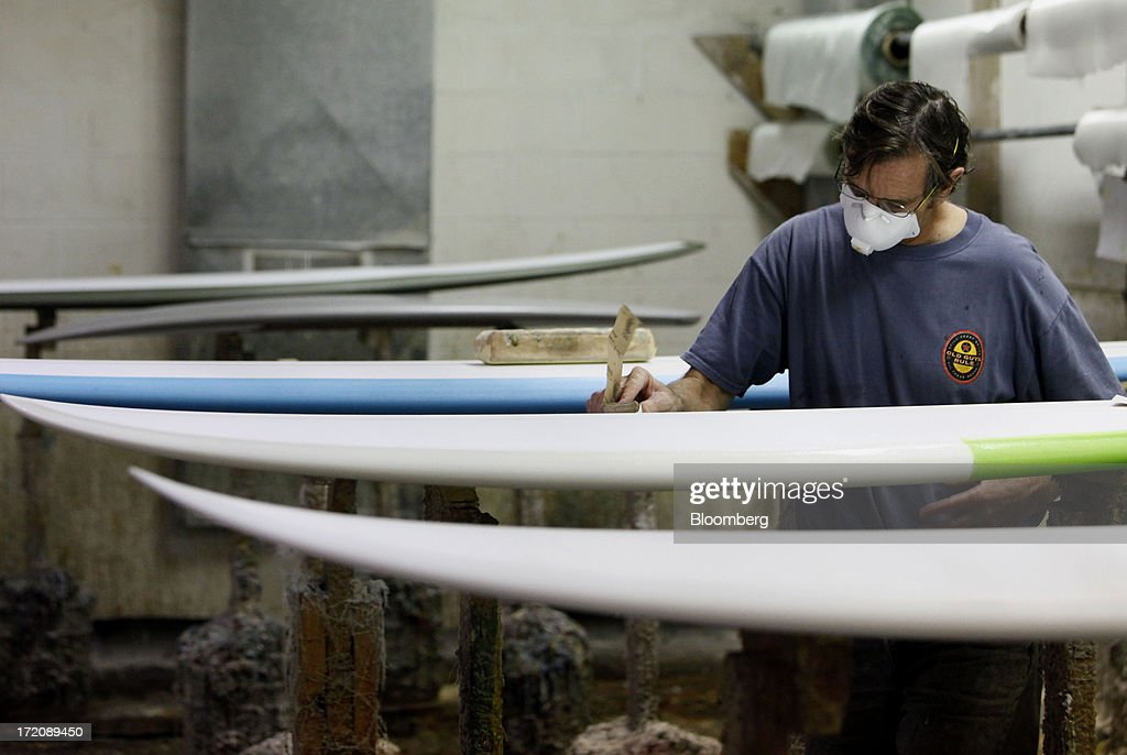 Employee Steve Burdette works on a Becker Surfboard during the resin and lamination process at the Mangiagli Manufacturing facility in Hermosa Beach, California, U.S., on Monday, July 1, 2013. The U.S. Census Bureau is scheduled to release factory orders figures on July 2. Photographer: Patrick T. Fallon/Bloomberg via Getty Images
