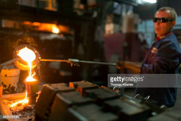 Employee taking a sample of liquid iron at the Ortrander Eisenhuette GmbH an ironworks on July 03 in Ortrand Germany The ironworks manufactures with...