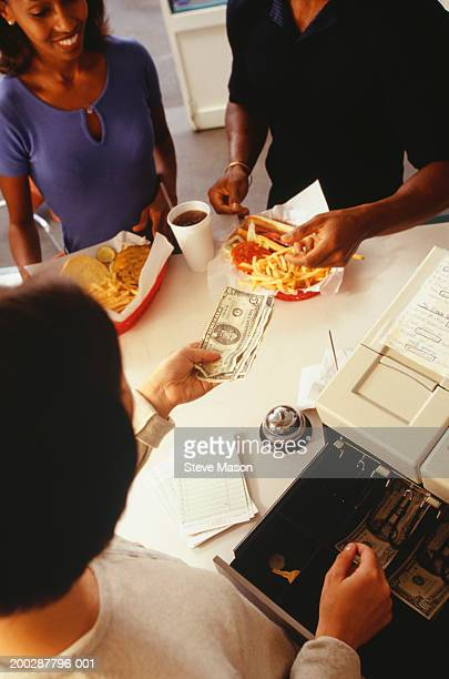 Employee taking payment for order in fast food restaurant