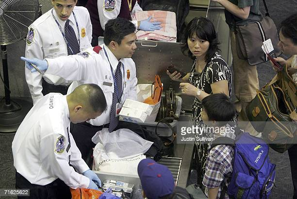 TSA employee talks to a United Airlines passenger after he confiscated containers of liquid from her carry on luggage at a security checkpoint at San...
