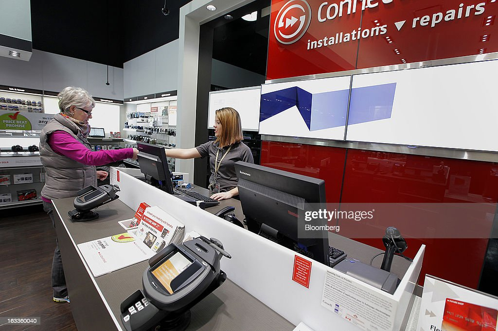 Employee Tamlyn Killoram, right, assists a customer at a Future Shop store in Vancouver, British Columbia, Canada, on Thursday, March 7, 2013. Future Shop, Canada's largest consumer electronics retailer, offers home and entertainment products, including televisions, computers, cameras, MP3 players, video games, computer add-ons, software, and audo and video systems. Photographer: Deddeda White/Bloomberg via Getty Images