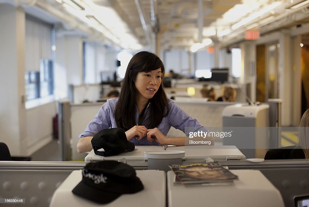 Employee Teresa Yee speaks with a co-worker during a media tour for the grand opening of Google Inc.'s new office in Toronto, Ontario, Canada, on Tuesday, Nov. 13, 2012. The office space encompasses five color-coded floors and features amenities such as a pool table, video games, mini-golf putting greens and a camping lounge where employees can hold meetings in a tent. Photographer: Brett Gunlock/Bloomberg via Getty Images