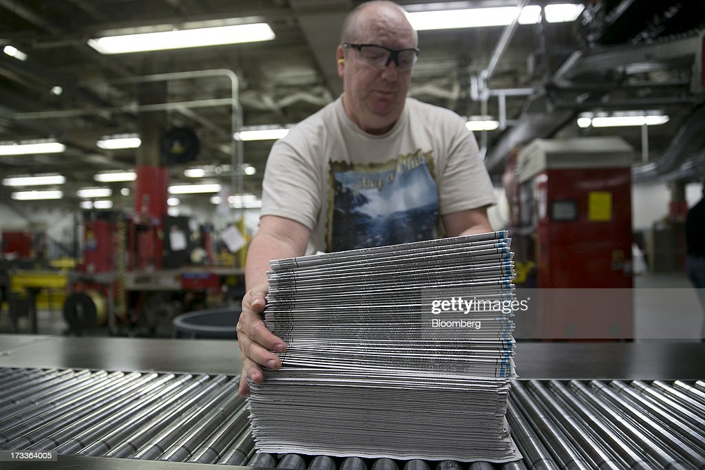 Employee Tom Hart arranges a stack of newspaper sections in the run of press area of the Washington Post newspaper production facility in Springfield, Virginia, U.S., on Friday, July 12, 2013. The Washington Post began publishing on Thursday, Dec. 6, 1877, and had a circulation of 10,000. The newspaper contained four pages and cost three cents a copy. Photographer: Andrew Harrer/Bloomberg via Getty Images