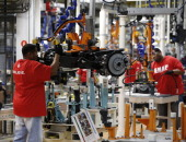 Employee Tracy Hunter lifts the front axle for 2015 Chrysler 200 at the company's Sterling Heights Assembly Plant in Sterling Heights Michigan US on...