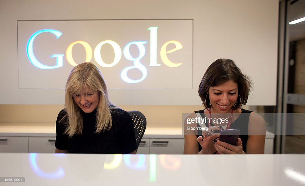 Employee Tracy McNeilly, left, smiles as Andrea Janus checks her phone while working at the front desk during a media tour for the grand opening of Google Inc.'s new office in Toronto, Ontario, Canada, on Tuesday, Nov. 13, 2012. The office space encompasses five color-coded floors and features amenities such as a pool table, video games, mini-golf putting greens and a camping lounge where employees can hold meetings in a tent. Photographer: Brett Gunlock/Bloomberg via Getty Images
