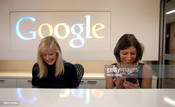 Employee Tracy McNeilly left smiles as Andrea Janus checks her phone while working at the front desk during a media tour for the grand opening of...