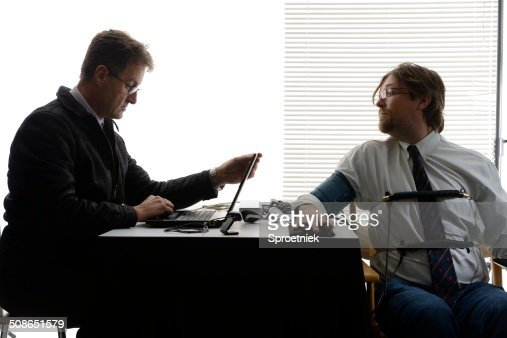 Employee tries to peer at polygraph test screen : Stock Photo