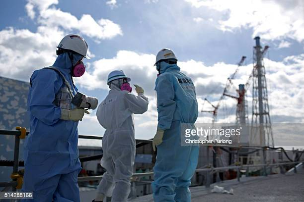 TEPCO employee uses a radiation monitor as they show a member of the media a destroyed reactor at Fukushima Daiichi nuclear power plant on February...