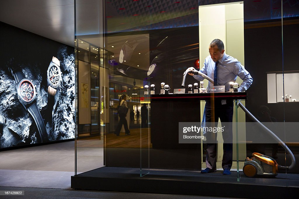 A employee vacuums a display of wristwatches at the Tudor booth during the Baselworld watch fair in Basel, Switzerland, on Thursday, April 25, 2013. The annual fair attracts 2,000 companies from the watch, jewelry and gem industries to show their new wares to more than 100,000 visitors. Photographer: Gianluca Colla/Bloomberg via Getty Images
