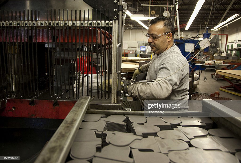 Employee Vincent Montez, a former Army Sergeant and Black Hawk helicopter mechanic, stamps metal plates at the E.J. Ajax & Sons metalforming company in Minneapolis, Minnesota, U.S., on Thursday, Dec. 6, 2012. The U.S. Federal Reserve is scheduled to release industrial production data on Dec. 14. Photographer: Ariana Lindquist/Bloomberg via Getty Images