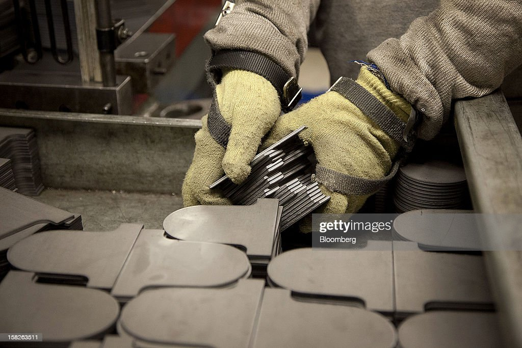 Employee Vincent Montez, a former Army Sergeant and Black Hawk helicopter mechanic, picks up metal plates to be stamped at the E.J. Ajax & Sons metalforming company in Minneapolis, Minnesota, U.S., on Thursday, Dec. 6, 2012. The U.S. Federal Reserve is scheduled to release industrial production data on Dec. 14. Photographer: Ariana Lindquist/Bloomberg via Getty Images