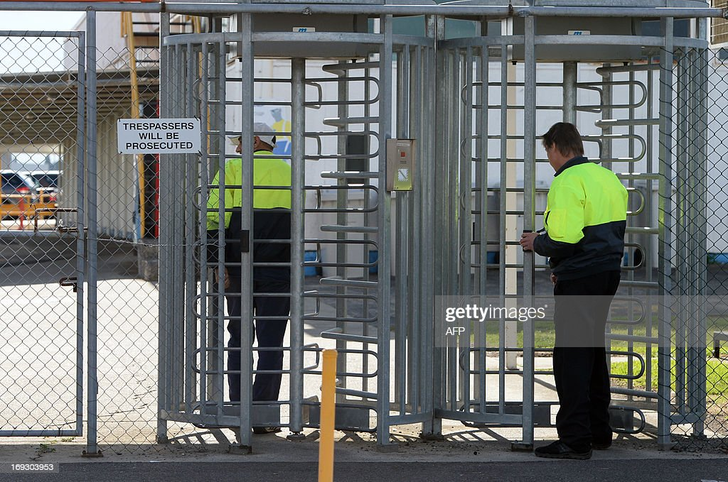 Employee walk through turnstiles at the site entrance of Ford's head office in Melbourne on May 23, 2013, as Ford announced it would cease making vehicles at its unprofitable Australian plants in 2016 and axe 1,200 jobs, ending an era that began in 1925 with the firm's first local car. Ford Australia chief executive Bob Graziano made the announcement as he revealed losses of 141 million AUSD (136 million USD) after tax in the last financial year and 600 million AUSD over the last five years. AFP PHOTO / Mal Fairclough