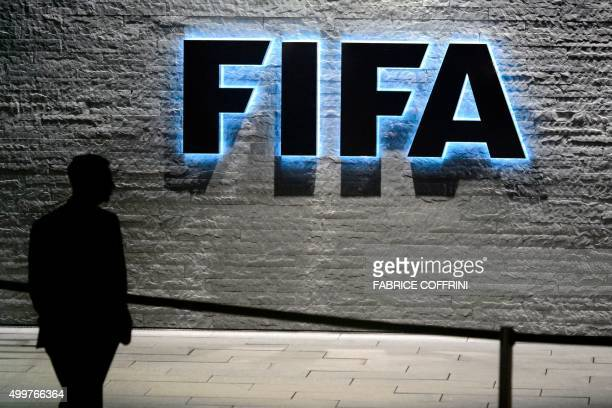 FIFA employee walks past a sign of the FIFA at the headquarters on December 3 2015 in Zurich The unprecedented corruption scandal engulfing FIFA...