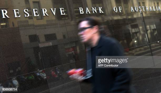 A employee walks past the Reserve Bank of Australia building in the central business district of Sydney on July 4 2017 Australia's central bank kept...
