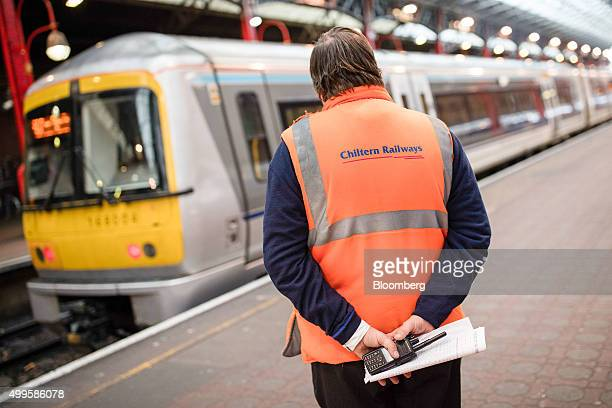 A employee watches the Chiltern Railway service to Birmingham New Street depart at London Marylebone railway station operated by The Chiltern Railway...