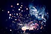 Employee welding steel with sparks, using MiG MAG welder