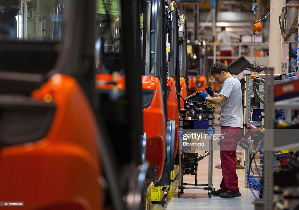 A employee works on a Linde H30 forklift truck as its sits on the production line at the Linde Material Handling GmbH factory, a unit of Kion Group AG, in Aschaffenburg, Germany, on Tuesday, Nov. 12, 2013. Kion Group AG, the German forklift-maker which listed shares in June, is looking to expand its global sales network via acquisitions to catch up with main competitor Toyota Industries Corp. Photographer: Krisztian Bocsi/Bloomberg via Getty Images