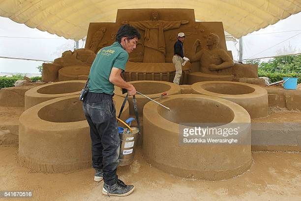 Employee works on a Sand sculpture of the Olympic Rings below the famous Christ the Redeemer statue of Jesus Christ titled Rio 2016 Olympic at the...