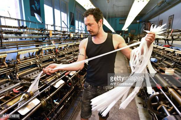 A employee works on a weaving loom in the factory of silk stockings and underwear manufacture company Arsoie Cervin on September 7 2017 in Sumene...