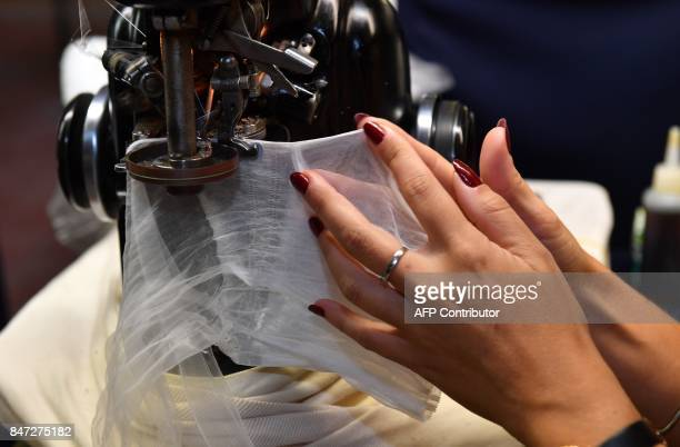 A employee works with a knitting machine to assemble stockings in the factory of silk stockings and underwear manufacture company Arsoie Cervin on...