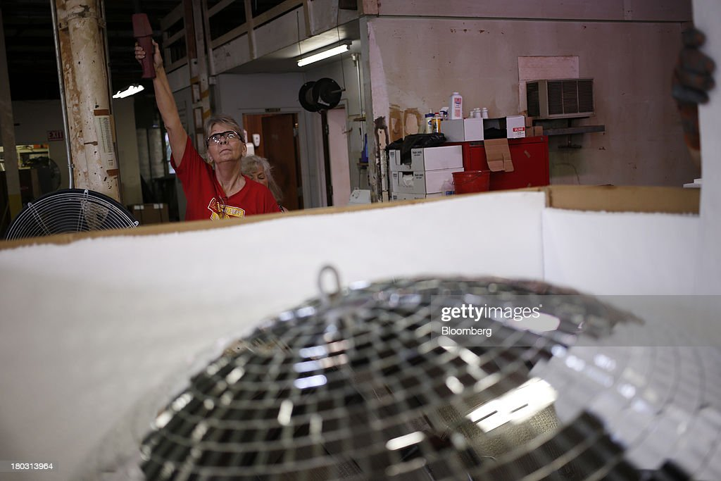 Employee Yolanda Baker lowers a four foot disco ball into a box at the Omega National Products manufacturing facility in Louisville, Kentucky, U.S., on Tuesday, Sept. 10, 2013. The U.S. Federal Reserve is scheduled to release industrial production figures on Sept. 16. Photographer: Luke Sharrett/Bloomberg via Getty Images
