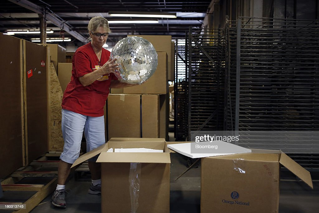 Employee Yolanda Baker unpacks a disco ball for a demonstration at the Omega National Products manufacturing facility in Louisville, Kentucky, U.S., on Tuesday, Sept. 10, 2013. The U.S. Federal Reserve is scheduled to release industrial production figures on Sept. 16. Photographer: Luke Sharrett/Bloomberg via Getty Images