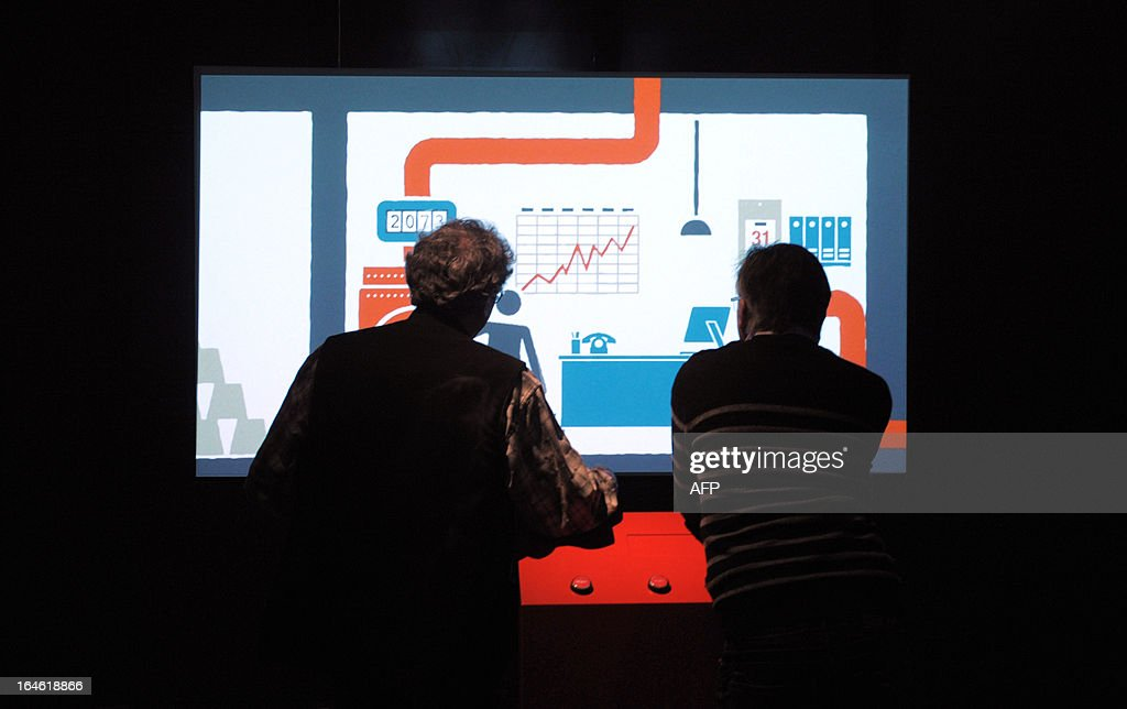 Employees add the finishing touch to an animated screen on March 25, 2013 ahead of the opening of the exhibition 'L'Economie: krach, boom, mue ?' at the Cite des Sciences in Paris. AFP PHOTO ERIC PIERMONT