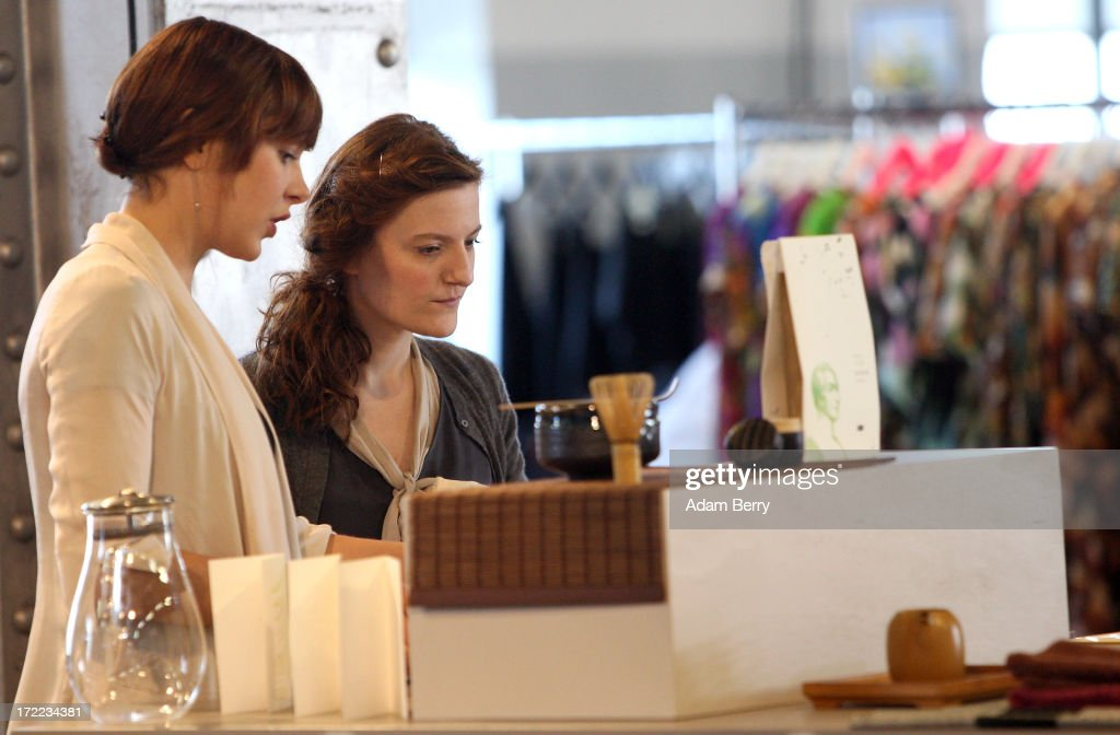 Employees adjust a stand with tea homeware products at the Capsule trade show at Collect - Showroom for Contemporary Fashion in Postbahnhof during Mercedes-Benz Fashion Week in Berlin on July 2, 2013 in Berlin, Germany.