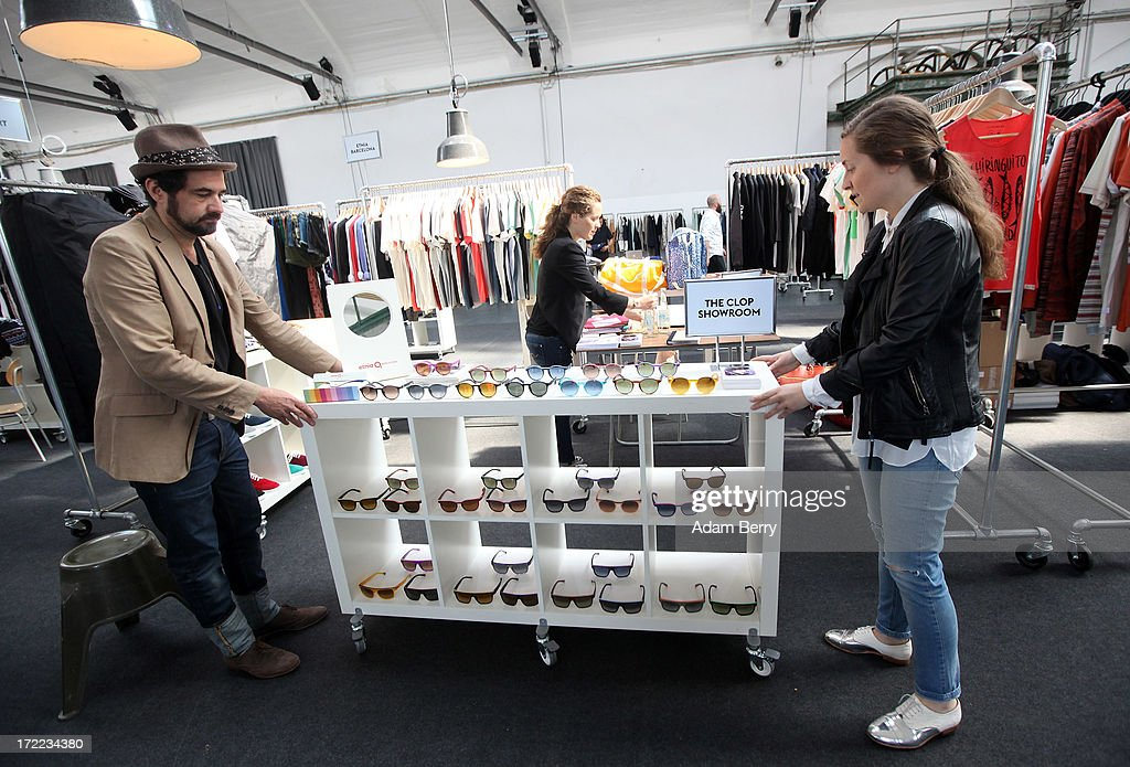 Employees adjust shelves of sunglasses by the brand The Clop Showroom during the Capsule trade show at Collect - Showroom for Contemporary Fashion in Postbahnhof during Mercedes-Benz Fashion Week in Berlin on July 2, 2013 in Berlin, Germany.
