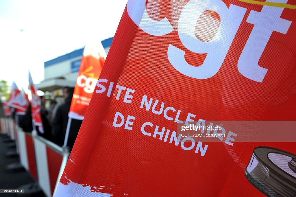 Employees and CGT union members rally in front of the Chinon nuclear power station to protest against the government's proposed labour reforms on May 26, 2016 in Avoine, central France. France faced fresh strikes after nuclear power station workers voted to join gathering protests against labour law reforms that have forced the country to dip into strategic fuel reserves due to refinery blockades. / AFP / GUILLAUME