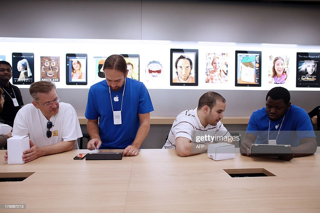 Employees and customers look at Apple's iPhone 5 smartphones and iPads in a new Apple store on July 6, 2013 in Rosny-sous-Bois, near Paris.