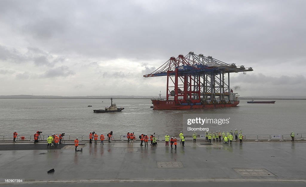 Employees and media watch from the dockside as the Zhen Hua 26, a semi-submersible heavy load carrier operated by Shanghai Zhenhua Heavy Industry Co. Ltd. (ZPMC), arrives with its cargo of ship-to-shore container cranes at the new DP World Ltd. London Gateway shipping terminal in Stanford-le-Hope, U.K., on Friday, March 1, 2013. DP World, which operates more than 60 terminals in six continents, said it is on track to open new capacity in Santos in Brazil, Jebel Ali in the United Arab Emirates and London Gateway in the U.K. this year. Photographer: Chris Ratcliffe/Bloomberg via Getty Images