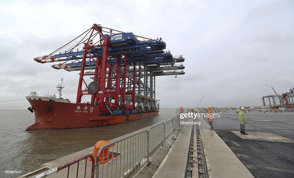 Employees and media watch from the dockside as the Zhen Hua 26, a semi-submersible heavy load carrier operated by Shanghai Zhenhua Heavy Industry Co. Ltd. (ZPMC), arrives at the DP World Ltd. London Gateway shipping terminal with its cargo of ship-to-shore container cranes in Stanford-le-Hope, U.K., on Friday, March 1, 2013. DP World, which operates more than 60 terminals in six continents, said it is on track to open new capacity in Santos in Brazil, Jebel Ali in the United Arab Emirates and London Gateway in the U.K. this year. Photographer: Chris Ratcliffe/Bloomberg via Getty Images