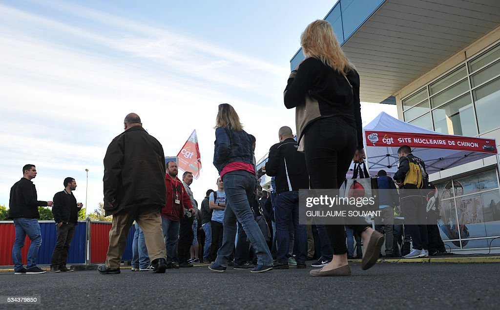 Employees and union members gather in front of the Chinon nuclear power station to protest against the government's proposed labour reforms on May 26, 2016 in Avoine, central France. France faced fresh strikes after nuclear power station workers voted to join gathering protests against labour law reforms that have forced the country to dip into strategic fuel reserves due to refinery blockades. / AFP / GUILLAUME