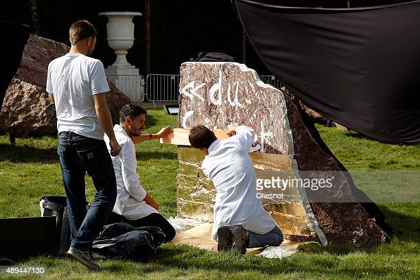 Employees apply gold leaf to cover the vandelism suffered by 'Dirty Corner' by BritishIndian sculptor Anish Kapoor in the garden of Chateau de...