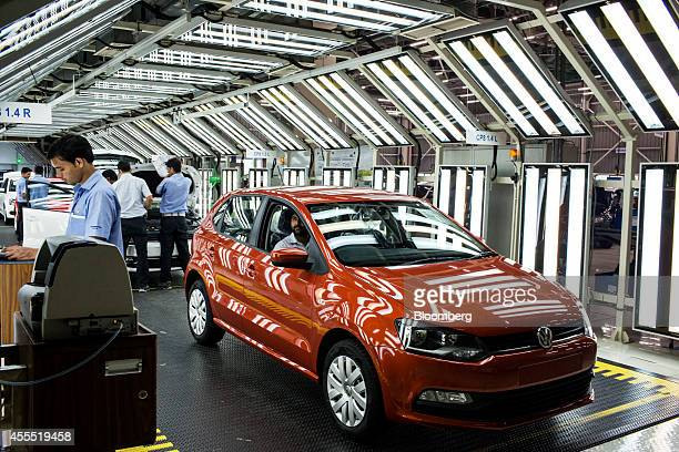 Employees apply the finishing touches to Volkswagen AG Vento automobiles on the production line at the Volkswagen India Pvt plant in Chakan...