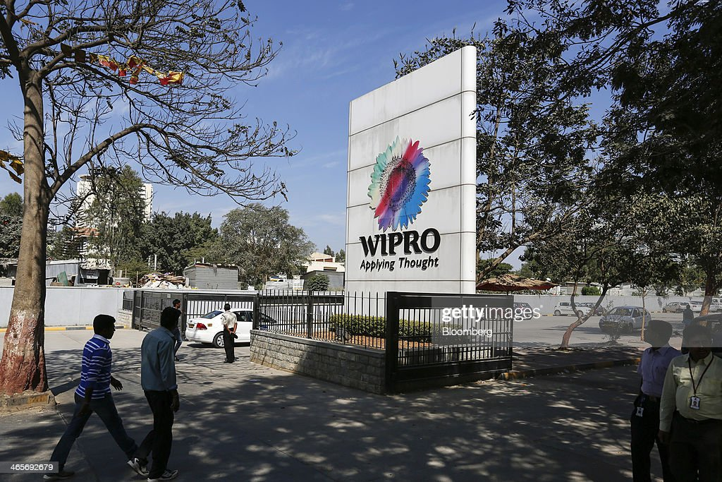 Employees approach Wipro Ltd. signage as they enter the company's campus in Bangalore, India, on Tuesday, Jan. 28, 2014. Worldwide spending on information technology will grow 3.1 percent to $3.8 trillion this year, with IT services set to climb 4.5 percent, researcher Gartner Inc. forecast Jan. 6. Photographer: Vivek Prakash/Bloomberg via Getty Images