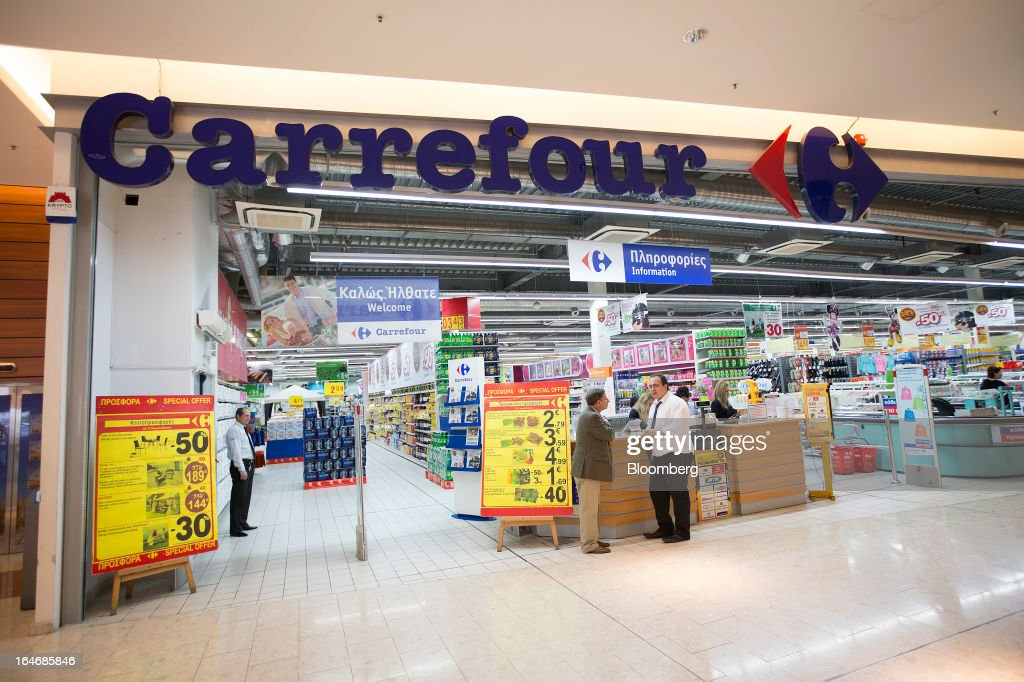 Employees are seen at the entrance to a Carrefour SA supermarket at the Mall of Cyprus in Nicosia, Cyprus, on Tuesday, March 26, 2013. Controls on capital movements to prevent money from draining out of the banking system -- allowed in exceptional circumstances under European Union law -- will remain for 'a matter of weeks,' Cypriot Finance Minister Michael Sarris said. Photographer: Simon Dawson/Bloomberg via Getty Images