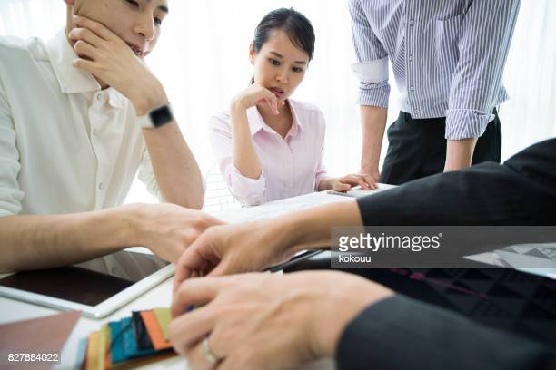 従業員は、材料と生地サンプルについて話しています。