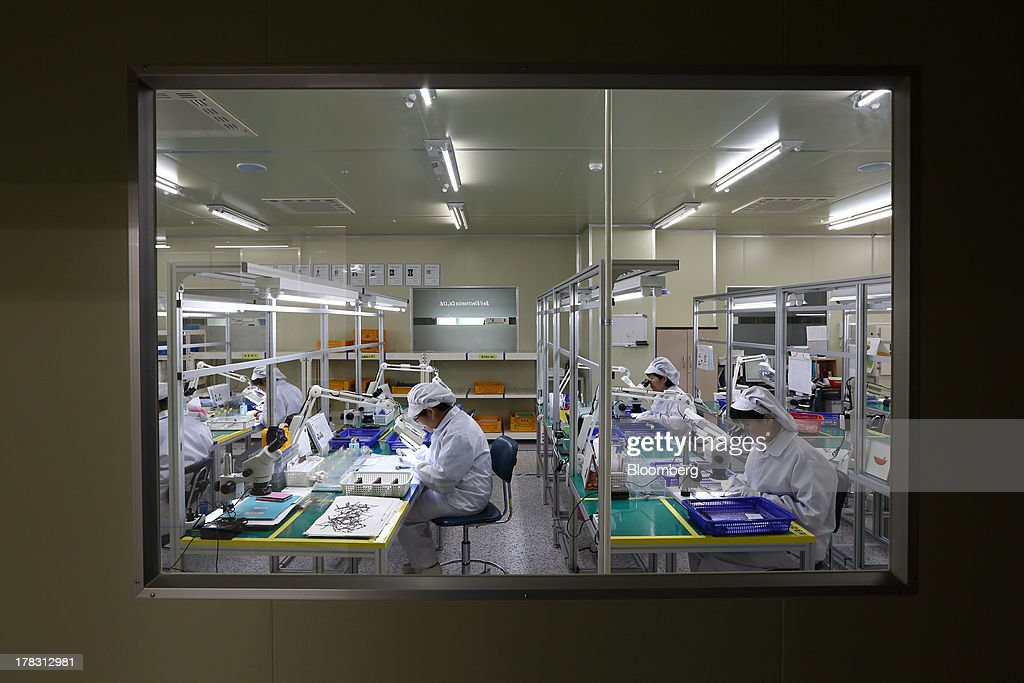Employees are viewed through a window as they inspect Flexible Printed Circuit Boards (F-PCB) through microscopes and magnifying glasses on the production line at the Seil Electronics Co. factory in Incheon, South Korea, on Wednesday, Aug. 28, 2013. South Korea has surpassed Brazil, Russia and India to become the second-biggest emerging stock market for the first time since 2006, as a stable won and record current-account surplus lure investors. Photographer: SeongJoon Cho/Bloomberg via Getty Images
