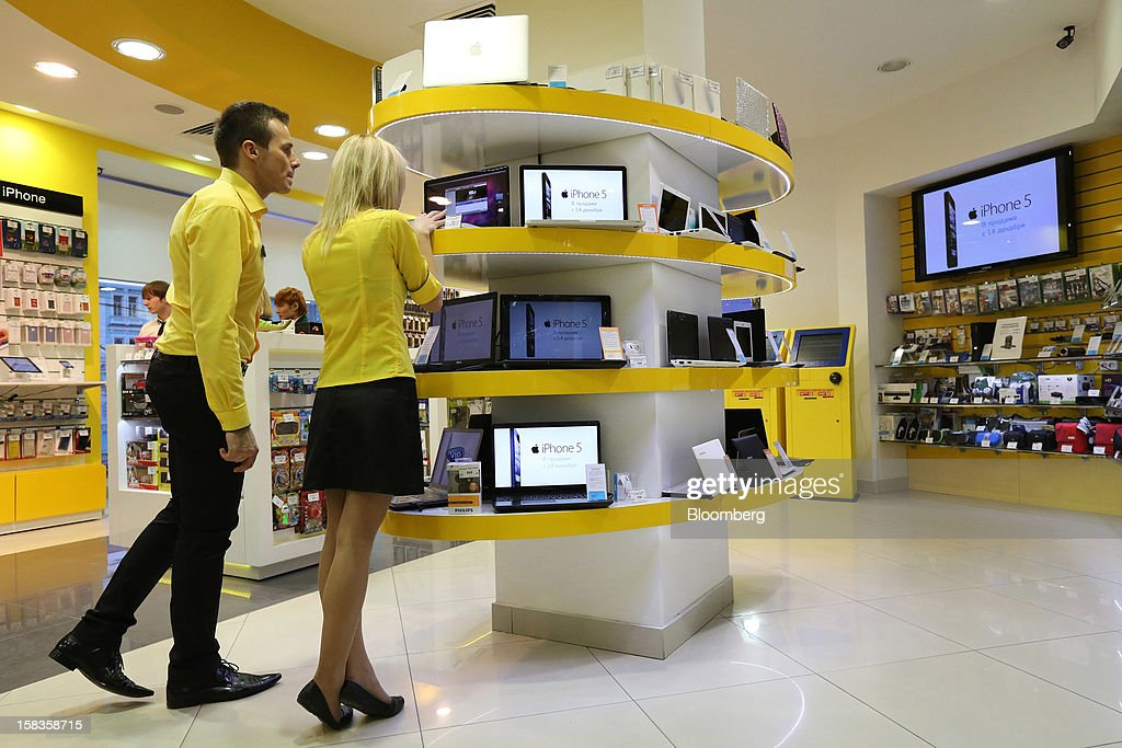 Employees arrange a display of laptop computers advertising Apple Inc. iPhone 5 smartphones inside a Euroset Holding NV mobile phone store in Moscow, Russia, on Thursday, Dec. 13, 2012. OAO MegaFon and its main shareholder billionaire Alisher Usmanov bought 50 percent of Euroset Holding NV in a deal that gives Russia's biggest handset retailer an enterprise value of $2.3 billion. Photographer: Andrey Rudakov/Bloomberg via Getty Images
