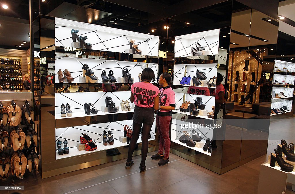 Employees arrange a display of women's footwear in the shoe department of a Topshop store, owned by Arcadia Group Ltd., on Oxford Street in London, U.K., on Thursday, Dec. 6, 2012. Philip Green, the billionaire owner of the Arcadia fashion business, sold a 25 percent stake in the Topshop and Topman retail chains to Leonard Green & Partners LP, the co-owner of the J Crew fashion brand, in a deal valuing the businesses at 2 billion pounds ($3.2 billion). Photographer: Simon Dawson/Bloomberg via Getty Images