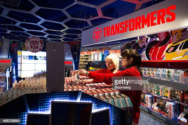 Employees arrange boxes of Transformer toys for sale in the new Hamleys Plc toy store on its opening day in Moscow Russia on Tuesday March 31 2015...