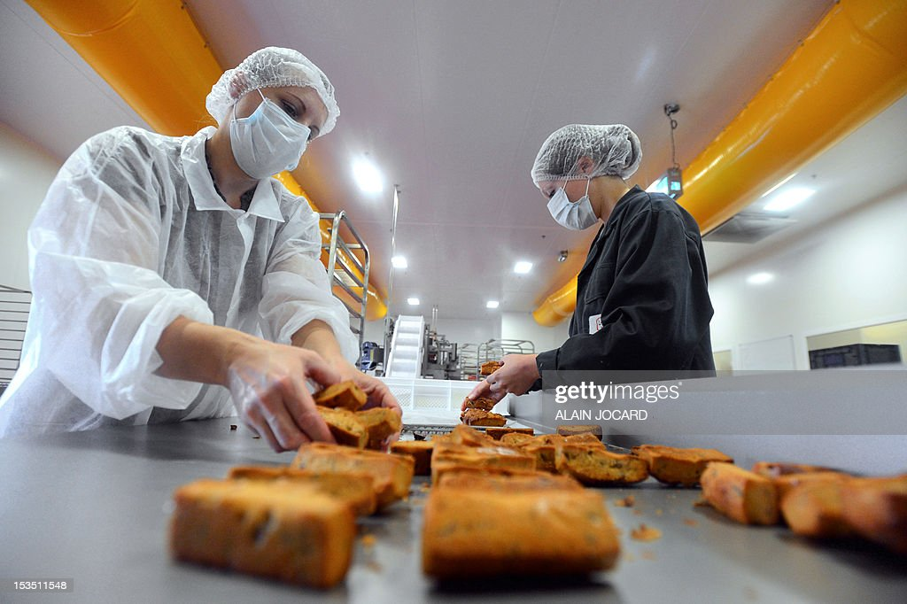 Employees arrange cakes on a railing on October 5, 2012 at a factory of French biscuits maker 'Saint-Michel' in Contres, western France.