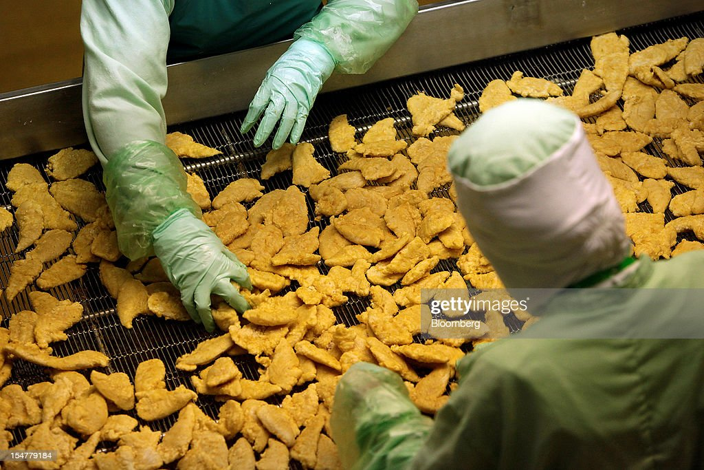 Employees arrange crumbed chicken pieces after frying in the precooked and frozen meat section at the Charoen Pokphand Foods Pcl (CP Foods) processing plant in Chok Chai, Nakhon Ratchasima province, Thailand, on Thursday, Oct. 25, 2012. CP Foods, controlled by billionaire Dhanin Chearavanont, is the nation's biggest meat and animal-feed producer. Photographer: Dario Pignatelli/Bloomberg via Getty Images