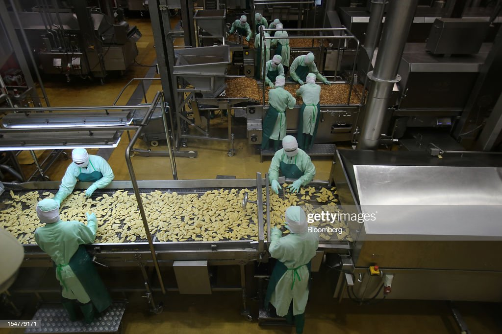 Employees arrange crumbed chicken pieces before, bottom, and after frying in the precooked and frozen meat section at the Charoen Pokphand Foods Pcl (CP Foods) processing plant in Chok Chai, Nakhon Ratchasima province, Thailand, on Thursday, Oct. 25, 2012. CP Foods, controlled by billionaire Dhanin Chearavanont, is the nation's biggest meat and animal-feed producer. Photographer: Dario Pignatelli/Bloomberg via Getty Images